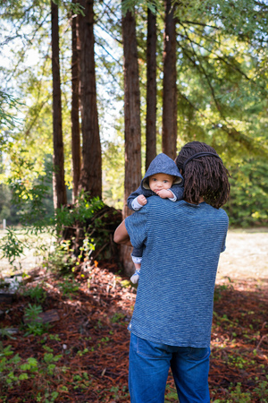 Mature man carrying baby son in forest,portrait