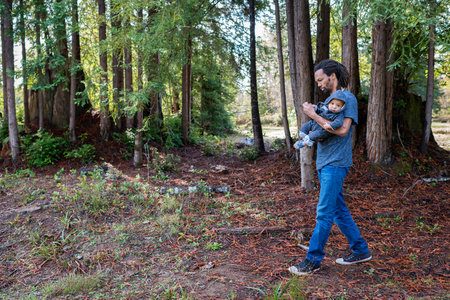 Mature man strolling in forest carrying baby son