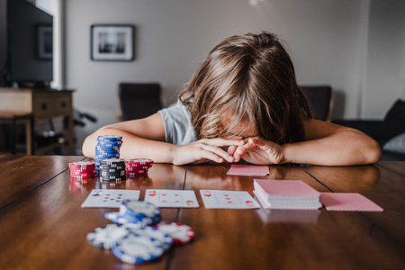 Girl playing cards at table with head down LANG_EVOIMAGES