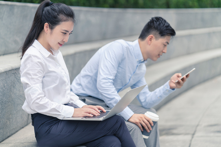 Young businesswoman and man using laptop and looking at smartphone on city seat,Shanghai,China