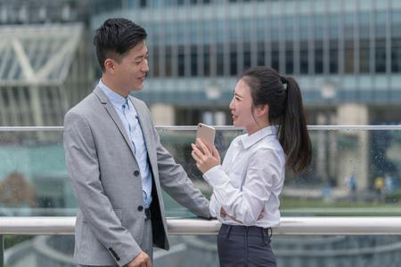 Young businesswoman and man talking in city,Shanghai,China
