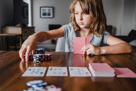 Girl playing cards at table,stacking gambling chips LANG_EVOIMAGES