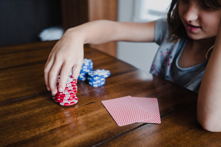 Girl playing cards at table,stacking gambling chips,close up LANG_EVOIMAGES