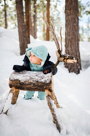 Baby boy ankle deep in forest snow leaning against wooden deer,South Lake Tahoe,California,USA