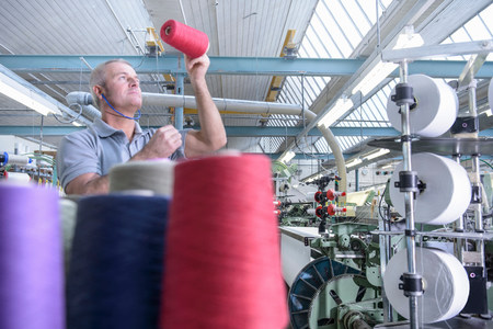 Worker inspecting bobbins of coloured thread in textile mill LANG_EVOIMAGES