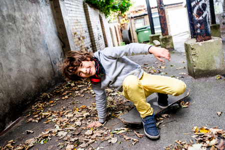 Boy falling off skateboard on street LANG_EVOIMAGES