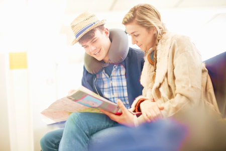 Young couple sitting in airport departure lounge, looking at map, planning trip, low angle view