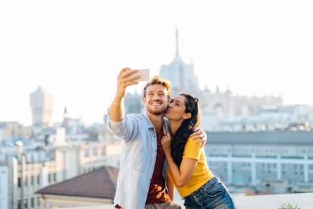 Couple taking selfie on edge of rooftop terrace, Milan, Italy