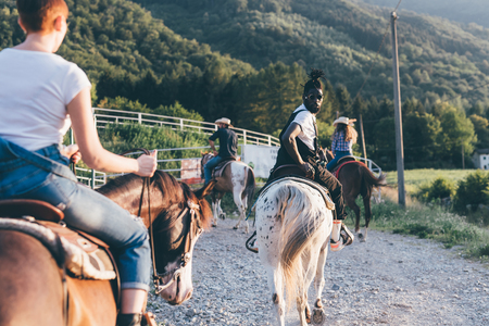 Adult friends riding horses on rural dirt track, rear view, Primaluna, Trentino-Alto Adige, Italy LANG_EVOIMAGES