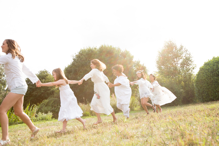 Female friends and family dancing in garden LANG_EVOIMAGES