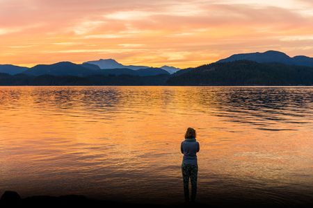 Young woman looking out at sunset, Quadra Island, Campbell River, Canada