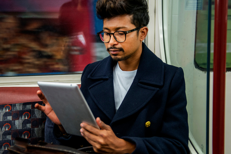 Businessman using digital tablet inside train