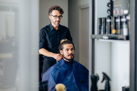 Male hairstylist putting on male customers cape at hair salon
