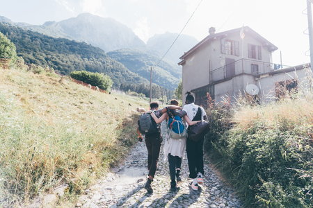 Young adult hiker friends with arms around each other on rural road, Primaluna, Trentino-Alto Adige, Italy LANG_EVOIMAGES