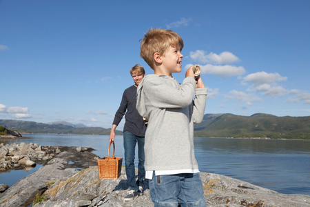 Boy and father carrying basket over inlet rock, Aure, More og Romsdal, Norway LANG_EVOIMAGES