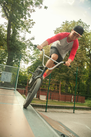 BMX cyclist doing nose wheelie on ramp