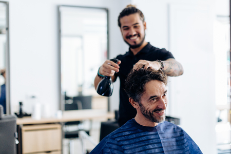 Male hairstylist spraying male customers hair in hair salon