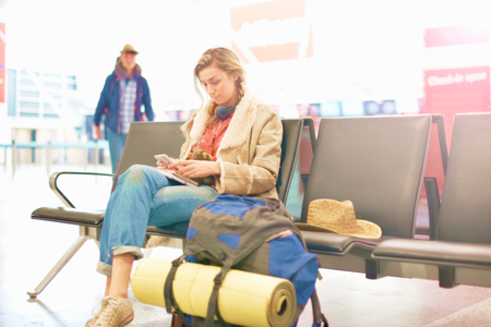 Young woman at airport, sitting with backpack beside her, using smartphone LANG_EVOIMAGES