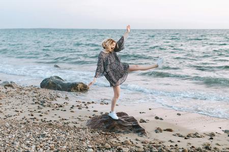 Young woman balancing on beach rock, Menemsha, Marthas Vineyard, Massachusetts, USA LANG_EVOIMAGES