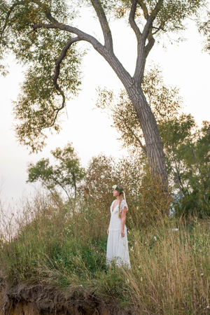 Bride in long grass by tree, Scarborough Bluffs, Toronto, Canada