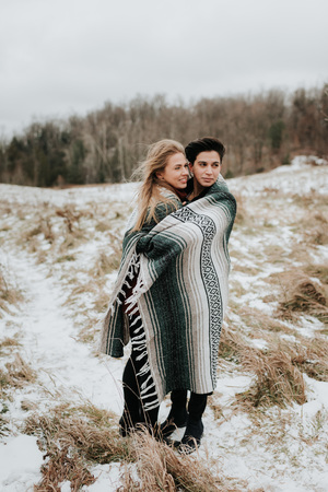 Couple wrapped in blanket in snowy landscape, Georgetown, Canada LANG_EVOIMAGES
