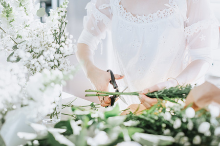 Young woman in white dress cutting white flowers, mid section