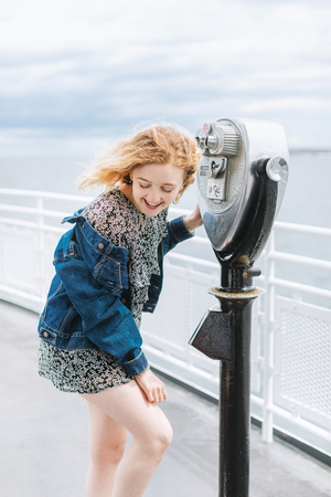 Young woman by coin operated binoculars on pier, Menemsha, Marthas Vineyard, Massachusetts, USA