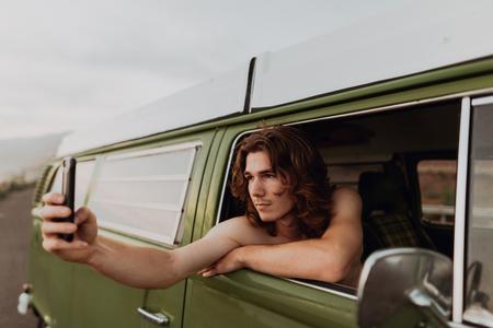 Man on van road trip taking selfie, Ventura, California, US LANG_EVOIMAGES