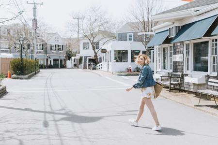 Young woman crossing road, portrait, Menemsha, Marthas Vineyard, Massachusetts, USA LANG_EVOIMAGES