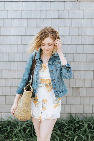 Young woman with straw bag in front of wall