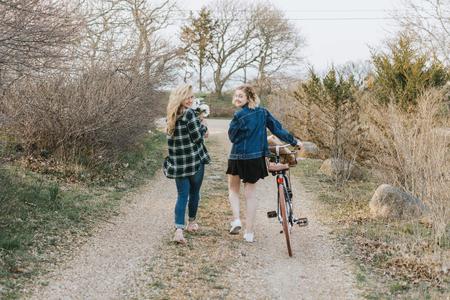 Two young women pushing bicycle on rural dirt track, rear view portrait, Menemsha, Marthas Vineyard, Massachusetts, USA
