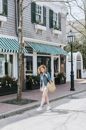 Young woman strolling along street carrying straw bag, Menemsha, Marthas Vineyard, Massachusetts, USA LANG_EVOIMAGES