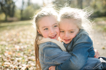 Sisters hugging in forest
