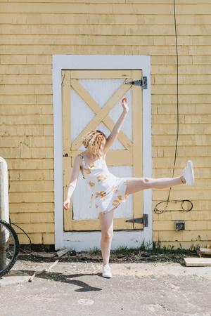 Young woman in front of building kicking her leg up, Menemsha, Marthas Vineyard, Massachusetts, USA
