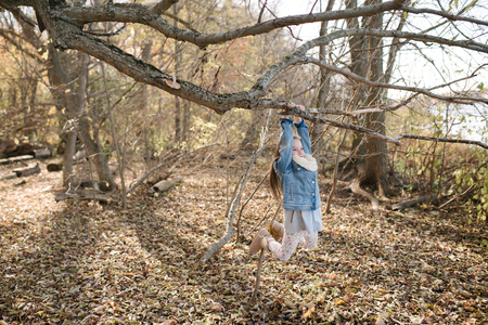 Little girl swinging on tree branch in forest LANG_EVOIMAGES