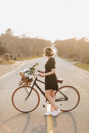 Young woman with bicycle looking sideways on rural road, Menemsha, Marthas Vineyard, Massachusetts, USA