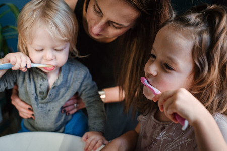 Mother helping children brush teeth LANG_EVOIMAGES