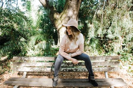 Woman relaxing on park bench, San Rafael, California, US
