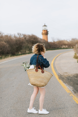 Young woman on rural road looking at lighthouse, rear view, Menemsha, Marthas Vineyard, Massachusetts, USA LANG_EVOIMAGES