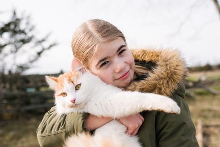 Girl cuddling cat in field