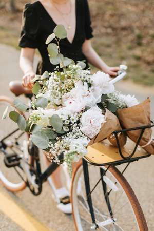 Young woman pushing bicycle with bunch of flowers on rural road, neck down, Menemsha, Marthas Vineyard, Massachusetts, USA LANG_EVOIMAGES