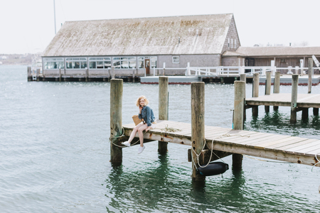 Young woman sitting on wooden pier, portrait, Menemsha, Marthas Vineyard, Massachusetts, USA LANG_EVOIMAGES