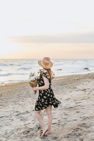 Young woman with bunch of flowers on windy beach, Menemsha, Marthas Vineyard, Massachusetts, USA