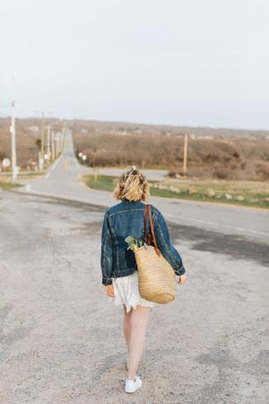 Young woman walking toward rural road, rear view, Menemsha, Marthas Vineyard, Massachusetts, USA