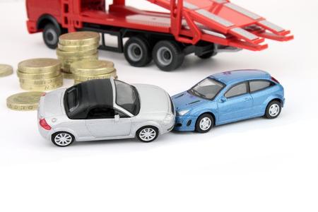 involving: Un incidente che coinvolge due automobili, con le monete e un camion guasto contro bianco in background Archivio Fotografico