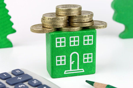 A green home with coins for the roof, representing savings to be made with an energy efficient home  Stockfoto