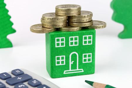 sterlina: Una casa verde con le monete per il tetto, che rappresentano un risparmio da effettuarsi con una casa efficiente