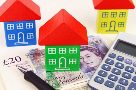 A house sitting on a pile of money, with a pen and calculator to symbolize house finance in the U k  Stockfoto
