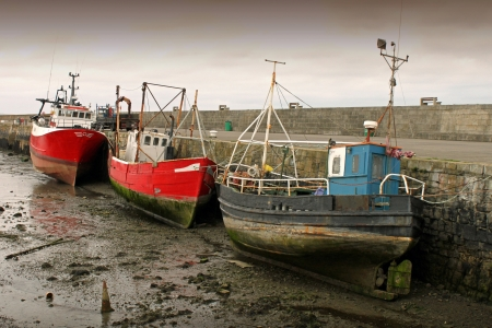 fishingboats: Three fishing boats at low tide in Howth harbour, Dublin.