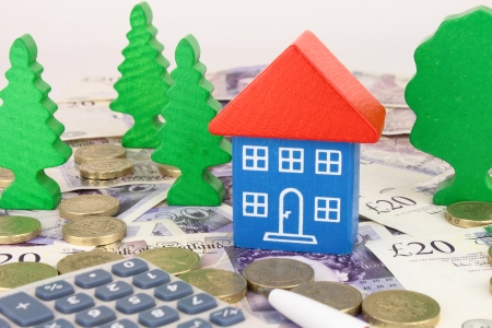 A toy house on sterling money, with coins and a calculator